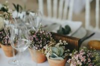 14 a wedding table runner composed of potted blooms and greenery is a cool sustainable idea to rock