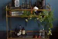 15 a stylish bar cart done with greenery, black touches and dark bottles plus pears on a plate