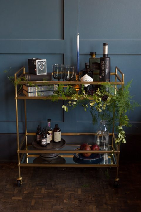 a stylish bar cart done with greenery, black touches and dark bottles plus pears on a plate