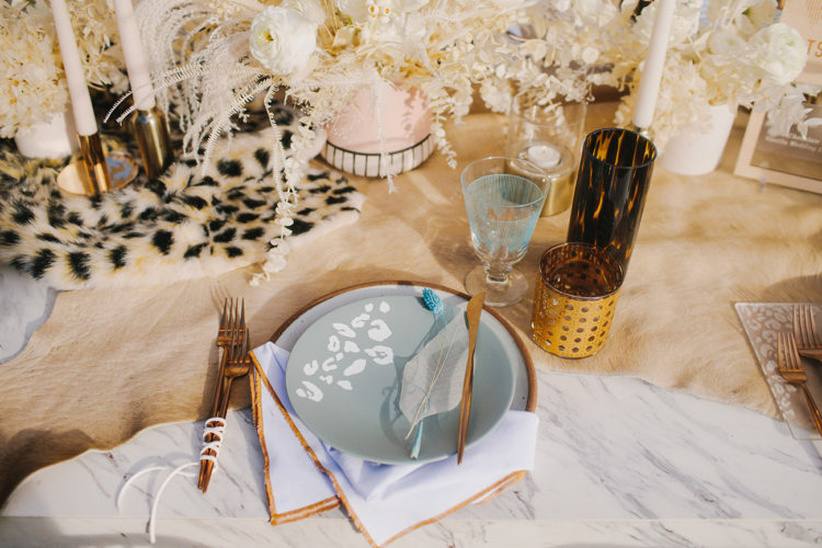 a unique wedding tablescape with a leopard print runner and plate is a chic and stylish idea