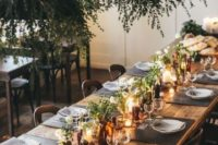 16 a stylish wedding tablescape with blooms in bottles, greenery arrangements over the table and candles
