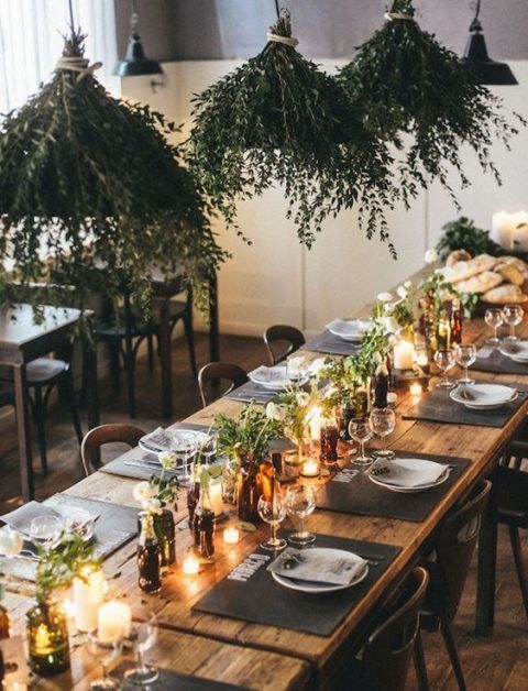 a stylish wedding tablescape with blooms in bottles, greenery arrangements over the table and candles