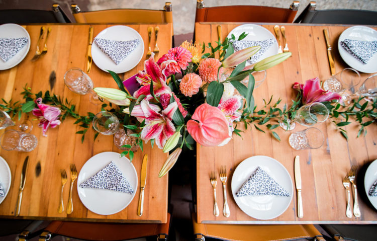 bright reception tables done with colorful florals and leopard print napkins plus ggold cutlery for more elegance