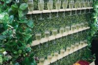 17 a greenery wall with shelves and champagne glasses plus various fruits and berries in a box is a cool and fresh idea to serve drinks