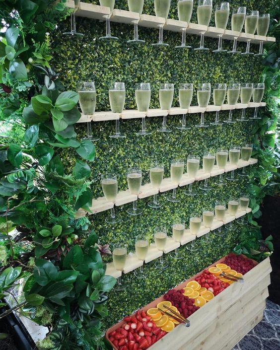 a greenery wall with shelves and champagne glasses plus various fruits and berries in a box is a cool and fresh idea to serve drinks