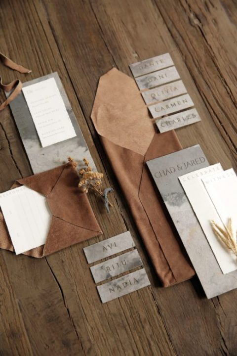 an elegant wedding invitation suite done with brown leather and grey watercolor paper