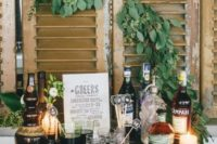 18 a chic and cozy vintage mini bar with various drinks, candles and greenery on the shutters over it