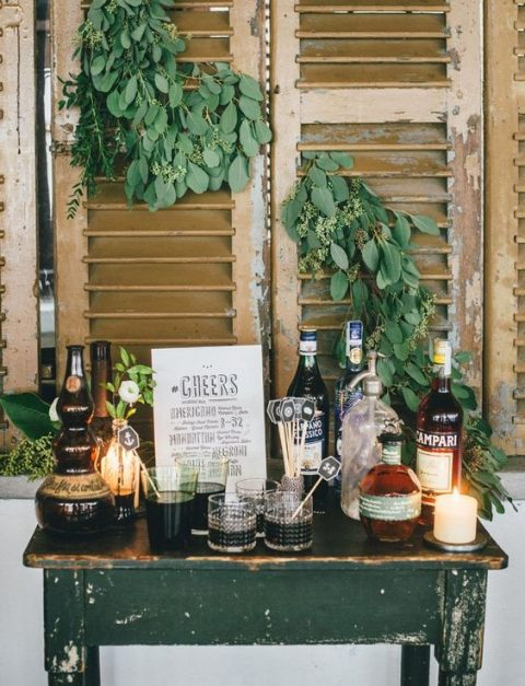 a chic and cozy vintage mini bar with various drinks, candles and greenery on the shutters over it
