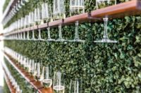 18 a living wall with wooden shelves and champagne glasses is a creative and chic way to serve drinks at the wedding