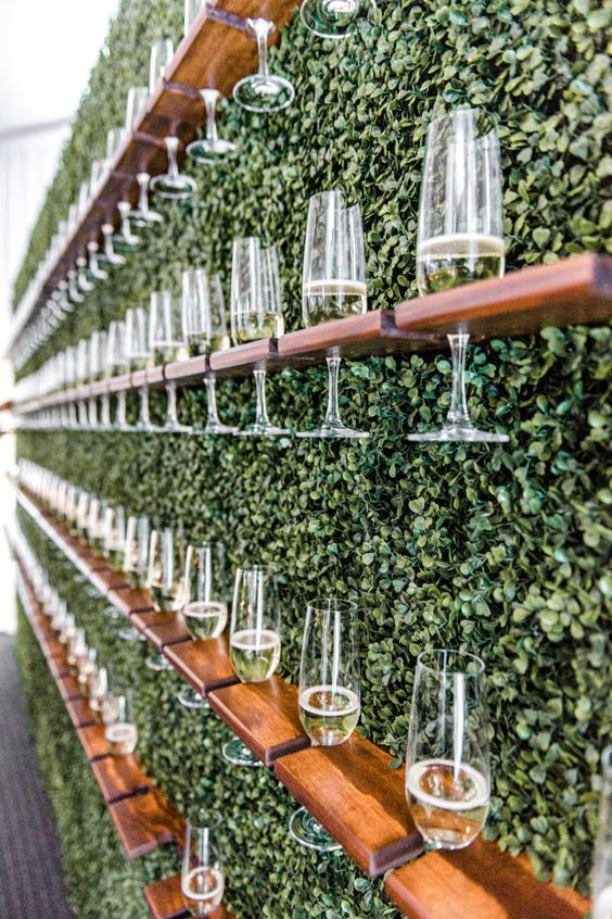a living wall with wooden shelves and champagne glasses is a creative and chic way to serve drinks at the wedding
