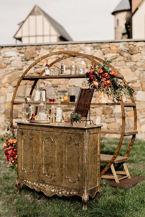 a chic rustic bar with a vintage sideboard, a round part with lots of bottles and blooms