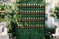 19 a simple living wall with champagne glass holders and fresh greenery on top plus candles