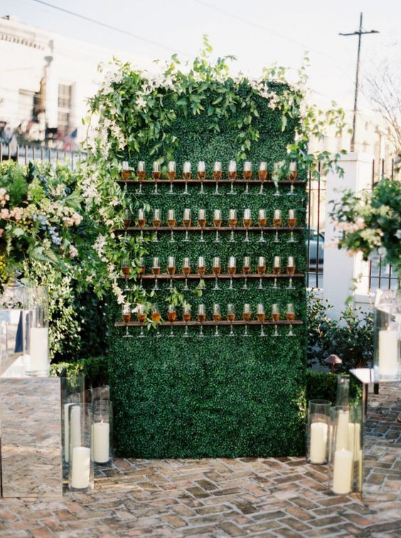 a simple living wall with champagne glass holders and fresh greenery on top plus candles