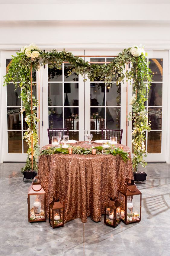 a wedding arch placed behind the sweetheart table to highlight it as much as possible