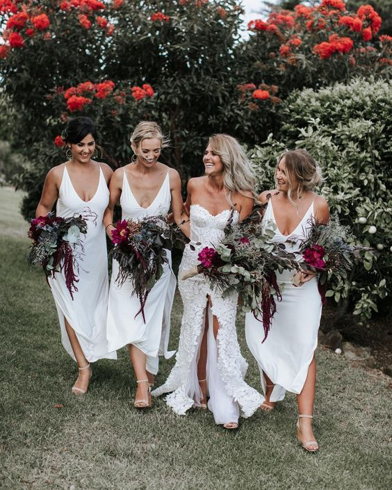 white midi slip bridesmaid dresses with deep necklines and side slits are a chic idea for a tropical wedding