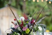 20 a boho moody wedding tablescape with a lush floral centerpiece with feathers, amber glasses and touches of gold