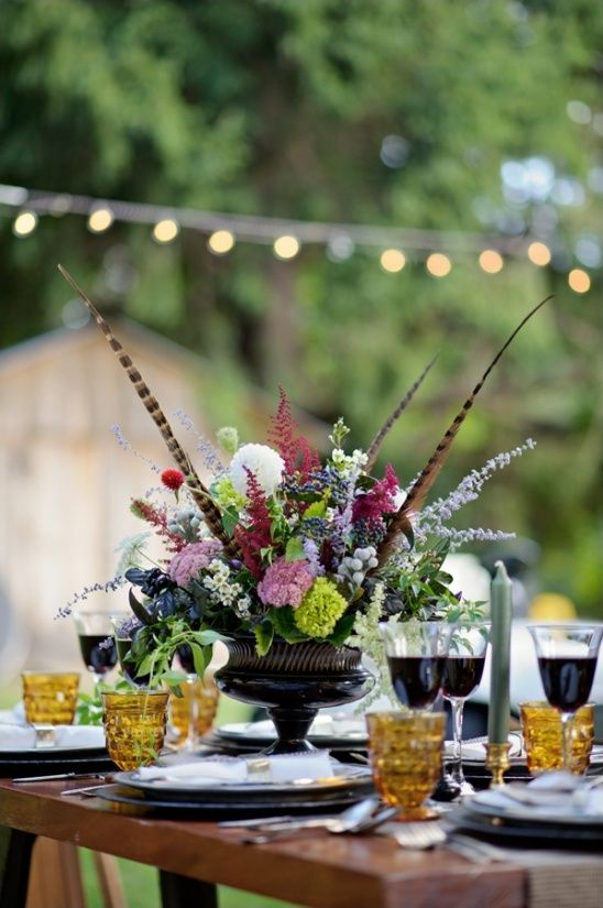 a boho moody wedding tablescape with a lush floral centerpiece with feathers, amber glasses and touches of gold