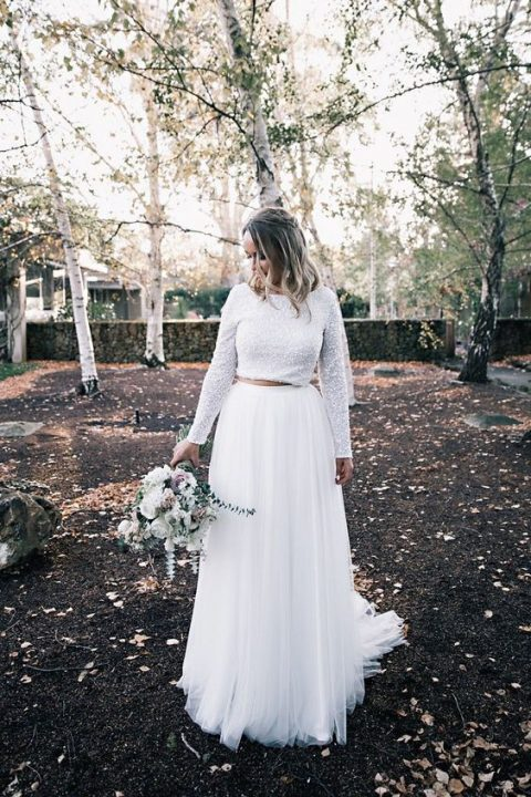 a modern and bold bridal separate with a white sequin crop top and long sleeves and a pleated white tulle maxi skirt