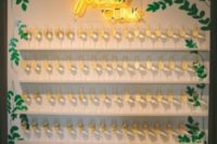 20 a stylish white champagne wall with shelves, greenery, a neon sign and elegant calligraphy for a modern wedding