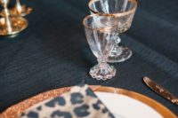 20 spruce up a refined dark tablescape with leopard print napkins and gold rim glasses