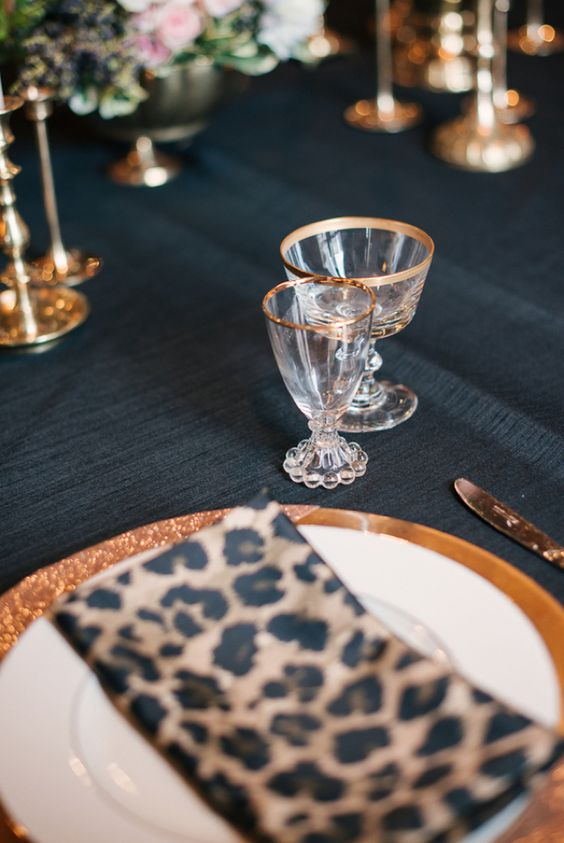 spruce up a refined dark tablescape with leopard print napkins and gold rim glasses
