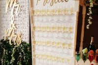 21 an elegant prosecco wall with gold calligraphy and holders for champagne glasses is a fresh and stylish idea