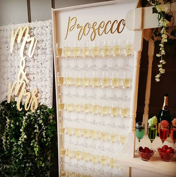 an elegant prosecco wall with gold calligraphy and holders for champagne glasses is a fresh and stylish idea