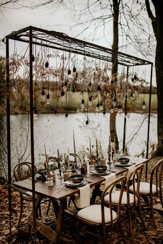 an industrial fall wedding tablescape with air plants, dark candles, bulbs and dried leaves over the table