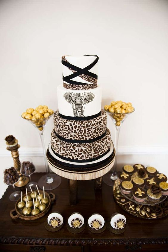 a safari-themed wedding cake with leopard tiers and a large elephant one is a bold idea to stand out