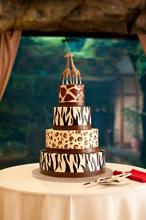 a safari-themed wedding cake with various kind sof animal prints and giraffe toppers is a bold idea