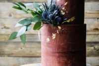 25 a matte burgundy wedding cake with gold leaf and thistles and greenery is chic and refined