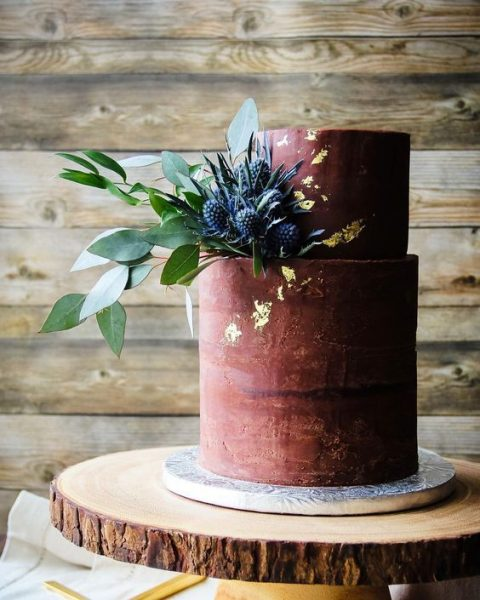a matte burgundy wedding cake with gold leaf and thistles and greenery is chic and refined