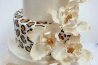 25 a white and leopard print wedding cake with large sugar blooms on top is a cool and fun idea to rock
