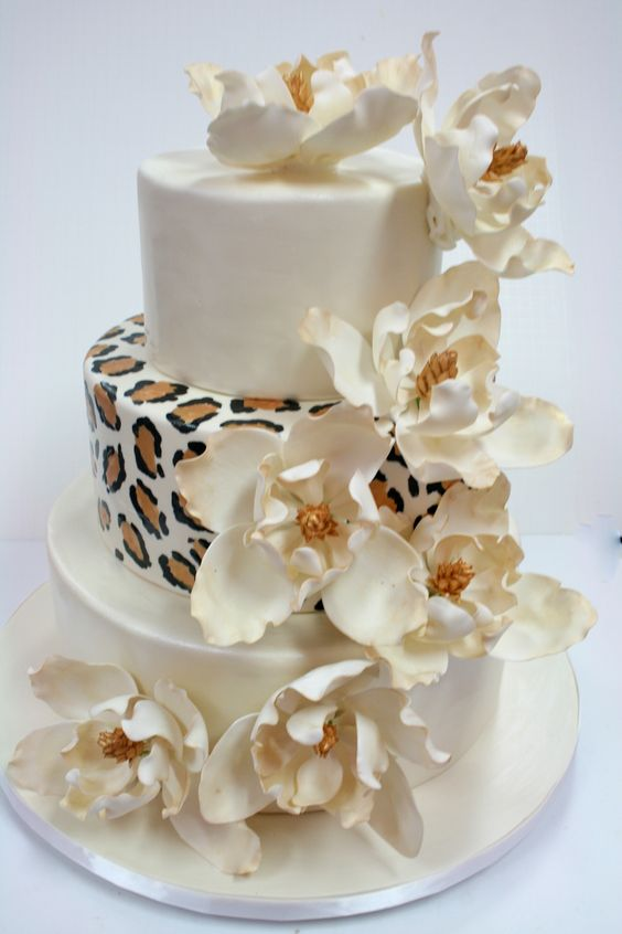 a white and leopard print wedding cake with large sugar blooms on top is a cool and fun idea to rock