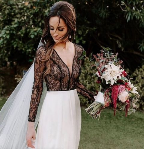 an edgy modern bridal outfit with a black lace top with long sleeves and a plain skirt plus a veil for an edgy look