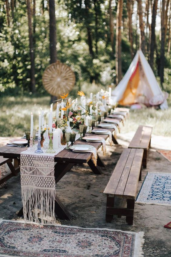 a boho tablescape with macrame, candles and bright blooms, benches and a teepee for a micro wedding