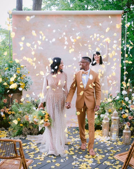 a bright summer micro wedding with yellow petals, candle lanterns and a blush watercolor backdrop is amazing