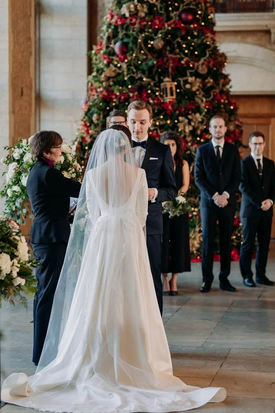 a cool micro holiday wedding indoors, with a large Christmas tree as a backdrop is a gorgeous idea