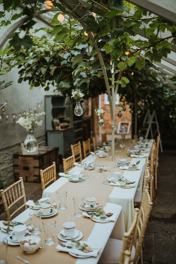 a cozy micro wedding reception with lush greenery, white blooms and elegant tableware is veyr intimate