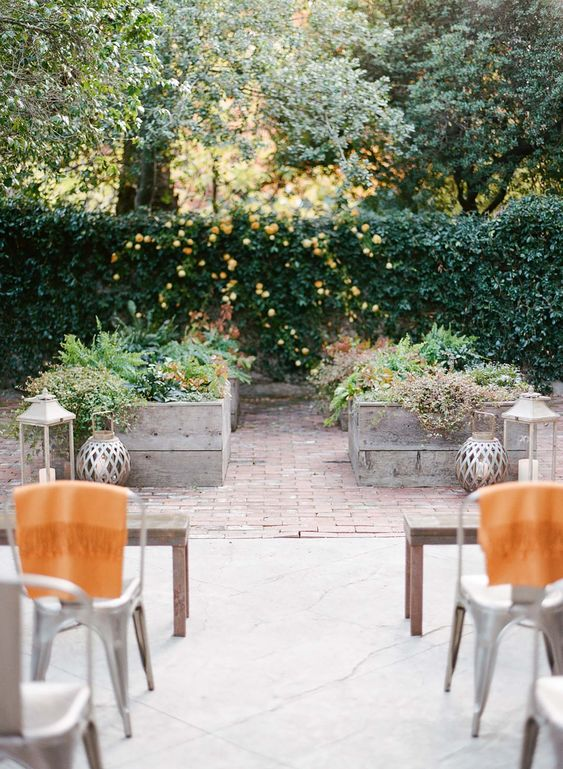 a garden micro wedding ceremony space with greenery, blooms, fruits and candle lanterns doesn't feel too large