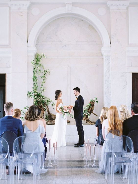 a romantic modern micro wedding ceremony space with greenery, driftwood and ghost guest chairs