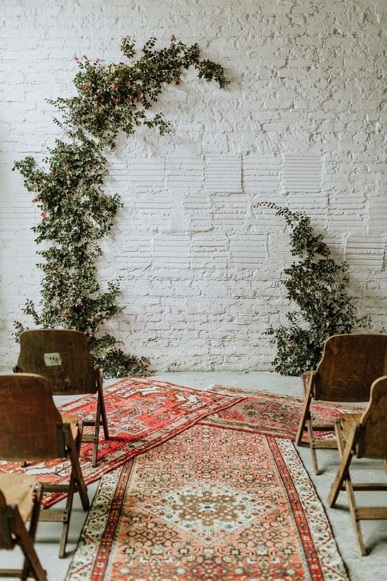 a simple micro wedding ceremony space with greenery, boho rugs and wooden chairs