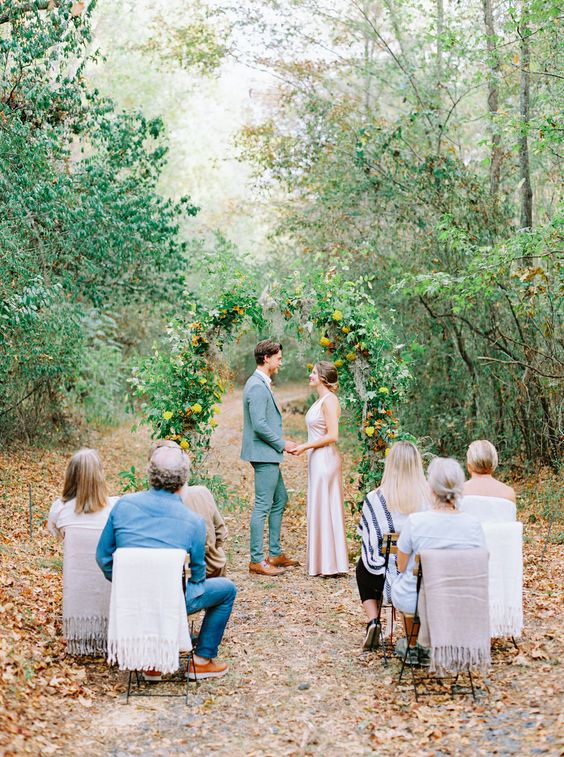 a small outdoor wedding ceremony space with a fall floral arch and greenery and just several guests