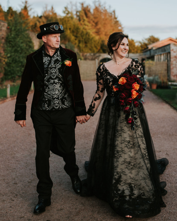 The bride was wearing a black lace V-neckline wedding dress with long sleeves, the groom was wearing a black suit and a whimsy shirt