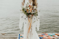 02 The bride was wearing a boho lace wedding dress with bell sleeves and a train by Rue De Seine