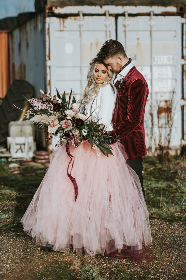 The bride was wearing a pink tutu, a white leather jacket and a half updo with waves