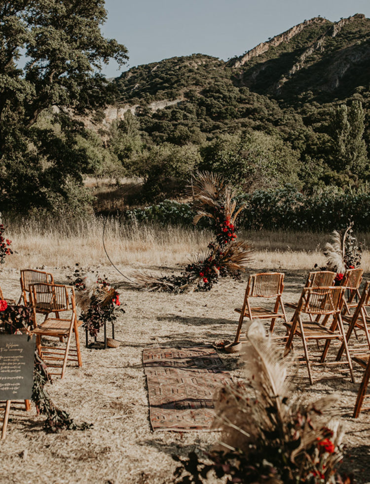 The wedding ceremony space was done with bright blooms, greenery, pampas grass and dried fronds
