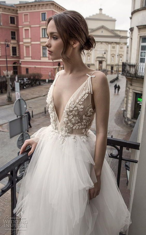 a delicate and refined wedding dress with an applique and embellished bodice with a plunging neckline and a full tulle skirt