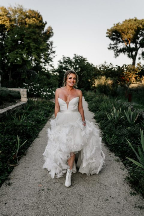 a gorgeous wedding ballgown with a plunging strapless neckline, a full feather skirt and white booties