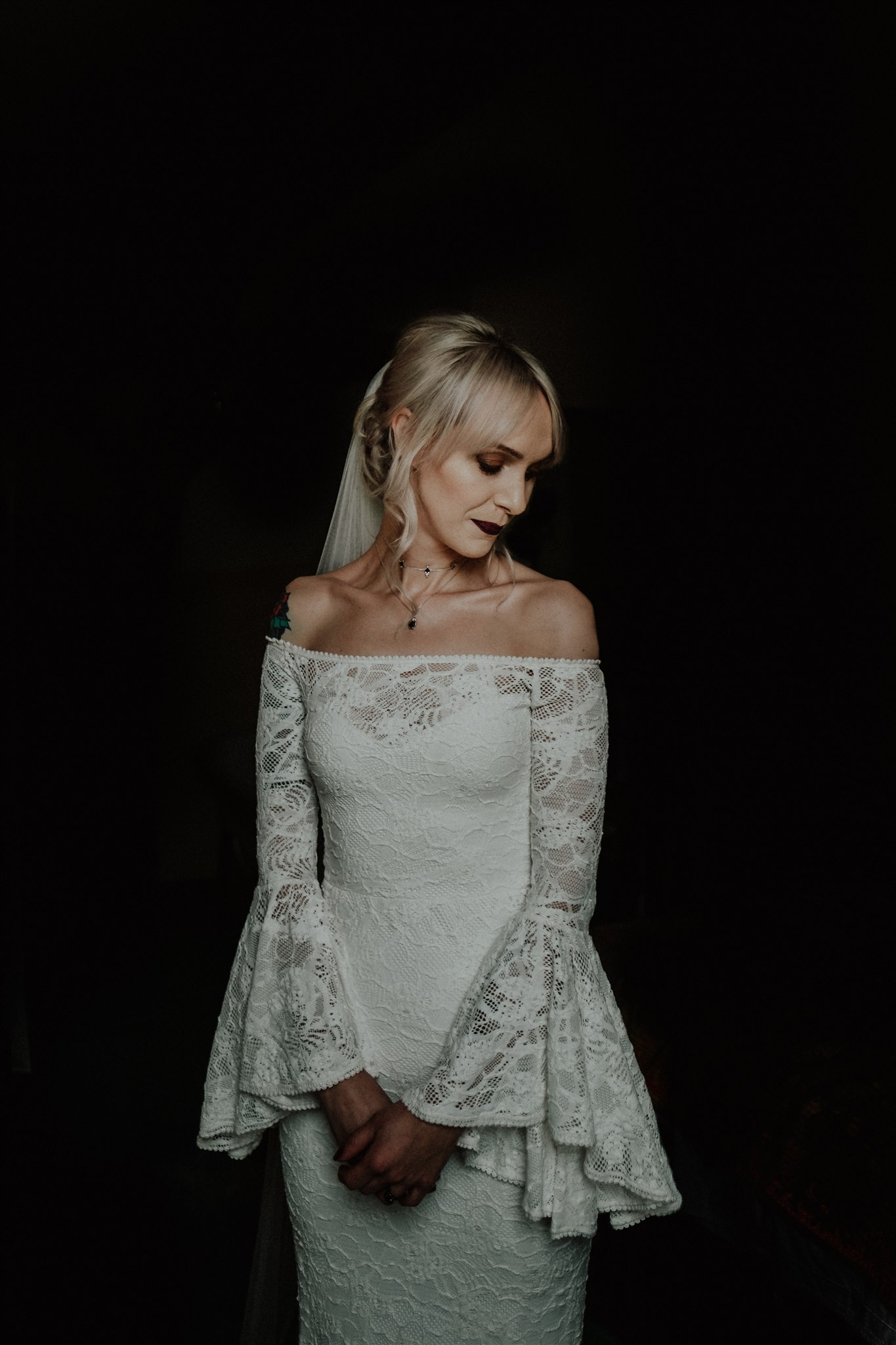 The bride was an off the shoulder lace sheath wedding dress with bell sleeves and a dark lipstick